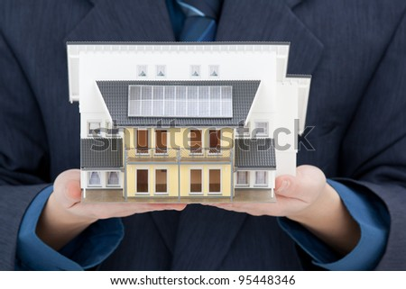 Real estate agent offer house with solar panels represented by model. - stock photo