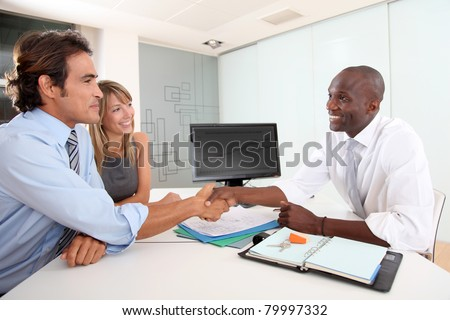 Real-estate agent shaking hand to house buyer - stock photo