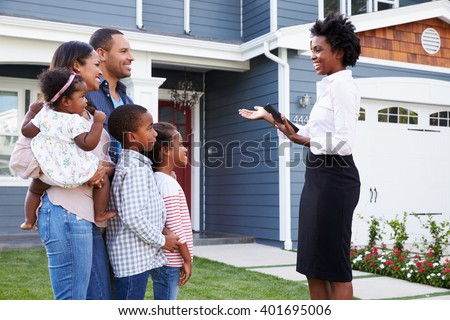 Real estate agent showing a family a house, closer in - stock photo