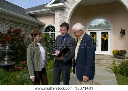 real estate agent showing a new home to a senior couple - stock photo