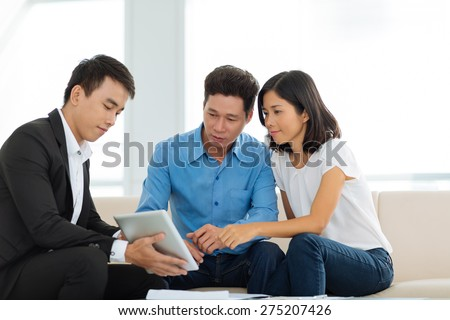 Real estate agent showing couple a house plan on the digital tablet - stock photo