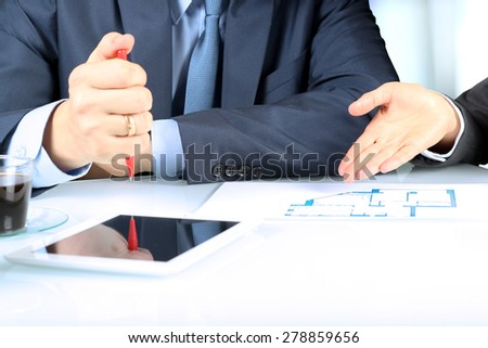 Real-estate agent showing house plans to a businessman. Focus on a hand - stock photo