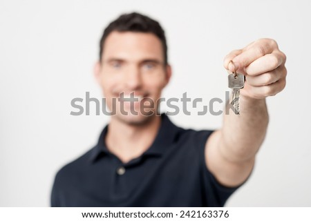 Real estate agent showing new house key - stock photo