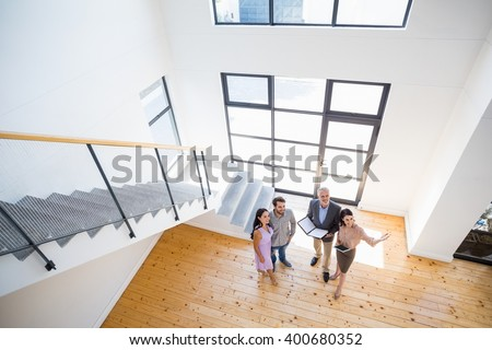Real estate agent showing new house to couple with digital tablet - stock photo