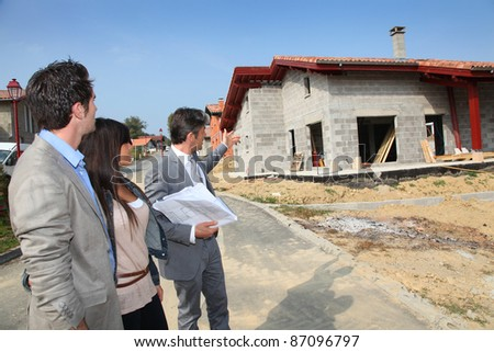 Real-estate agent showing plan to young home investors - stock photo