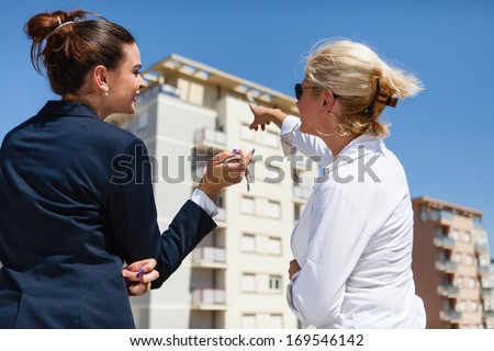 Real Estate agent shows to the beautiful young woman her new home.  - stock photo
