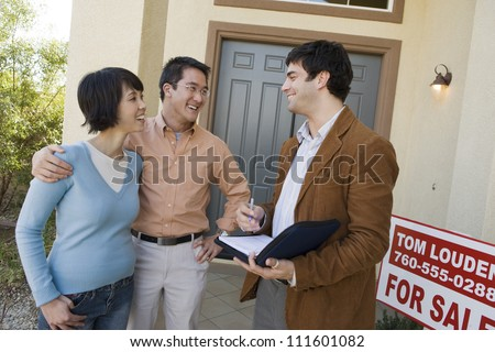 Real estate agent with asian couple buying new house - stock photo