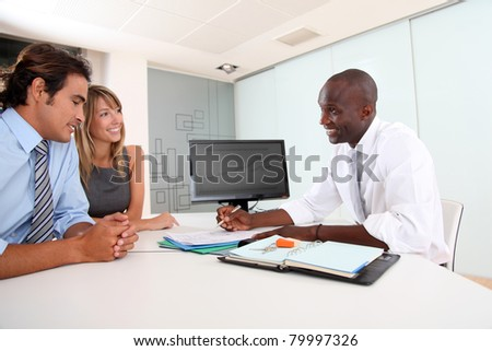 Real-estate agent with couple in office