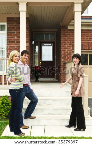 Real estate agent with couple welcoming to new home - stock photo