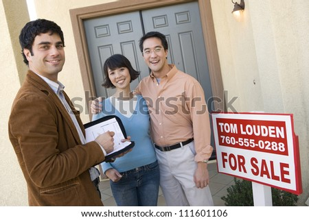 Real estate agent with happy asian couple buying new house - stock photo