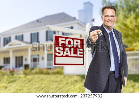 Real Estate Agent with House Keys in Front of For Sale Sign and Home. - stock photo