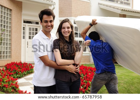 Real estate and moving home: Couple showing keys and relocator carrying mattress into their new home - stock photo
