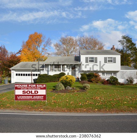Real Estate (another success let us help you buy sell your next home) sign Suburban High Ranch house autumn day residential neighborhood blue sky clouds USA - stock photo