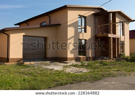 Real Estate Architectural Exterior House Building Design on Grassy Landscape. - stock photo