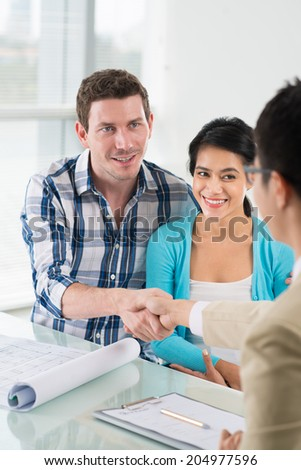 Real estate broker and his client shaking hands - stock photo