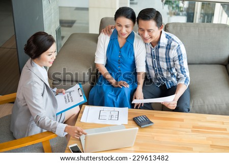 Real estate broker showing the project of the house to the family - stock photo