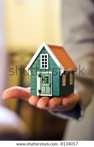 Real estate business - woman holding a miniature house in hand - stock photo