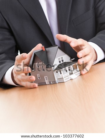 Real estate concept - business man hands around home architectural model - stock photo