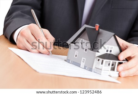 Real estate concept - business man signs contract behind home architectural model - stock photo