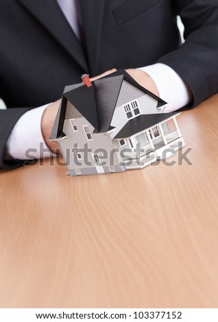 Real estate concept - businessman hands behind house architectural model