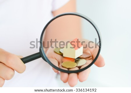 Real estate concept - coins and house architectural model in woman hand under magnifying glass - stock photo