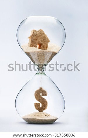 Real estate concept. Dollar sign made out of falling sand from house flowing through hourglass - stock photo