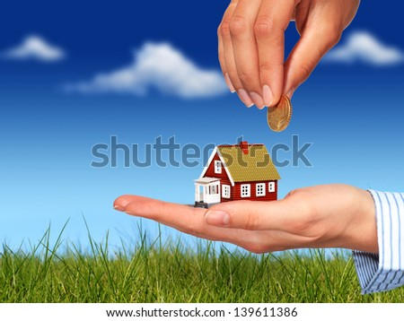 Real estate concept. Hand with coin and house. - stock photo