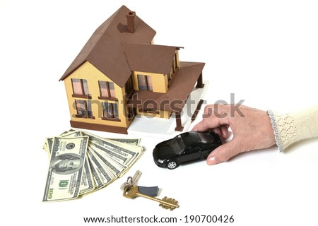 Real estate concept. miniature house, car, keys and dollars on a white background
