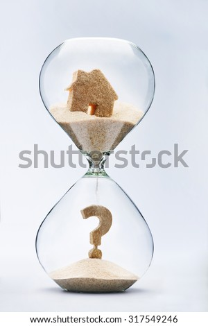 Real estate concept. Question mark made out of falling sand from house flowing through hourglass