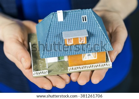 real estate concept - small scale model family house in womans hands - stock photo