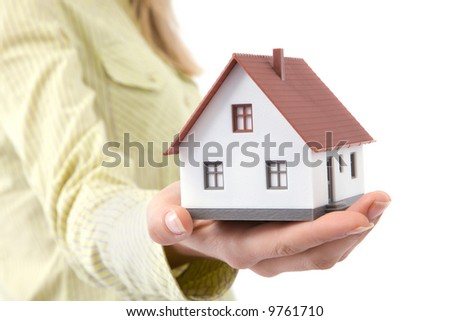 real estate concept with businesswoman holding mini house - stock photo
