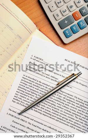 Real estate contract, pen and calculator