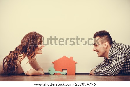real estate, family and couple concept - smiling couple lying on floor with symbol house and key daydreaming at home, vintage filter - stock photo