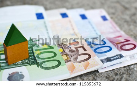 Real estate finance concept with mini house and Euros