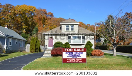 Real Estate For Sale Open House Welcome sign on front yard lawn of suburban bungalow style home residential neighborhood clear blue sky USA - stock photo