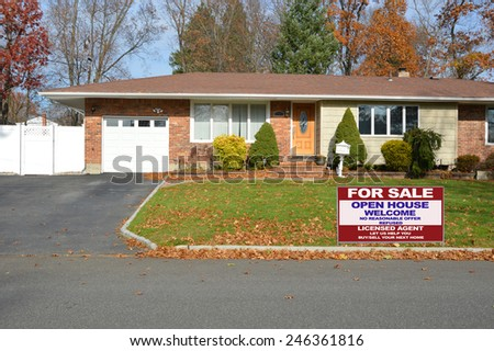 Real estate for sale open house welcome sign suburban brick ranch style home white picket fence blacktop driveway autumn blue sky day residential neighborhood USA - stock photo