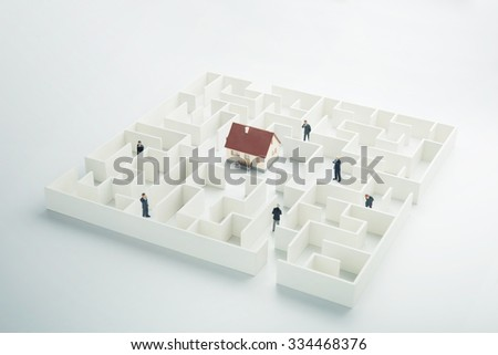 Real estate labyrinth. Toy house hidden inside a maze - stock photo