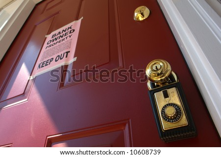 Real estate lock box and bank owned keep out bank owned financial lender foreclosure notice on a house door (fictitious document with authentic legal language) - stock photo