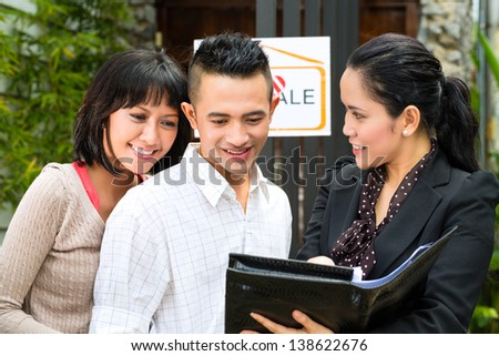 Real estate market - young Indonesian couple looking for real estate apartment or house to rent or buy, the realtor showing a document - stock photo