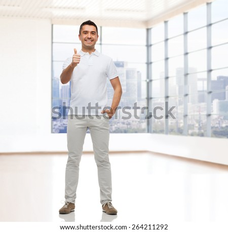 real estate, sale, business, gesture and people concept - smiling man showing thumbs up over empty apartment or office room with big window and city view background - stock photo