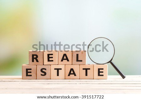 Real estate search sign with a magnifying glass on a table - stock photo