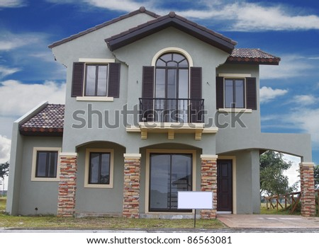 Real estate sign in front of a house for sale with blue clouds. - stock photo