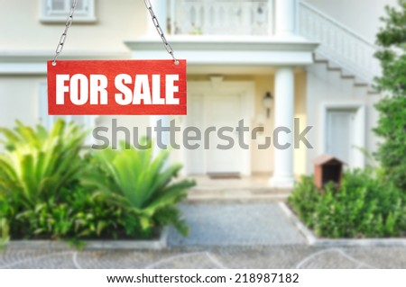 Real estate sign in front of new house for sale - stock photo