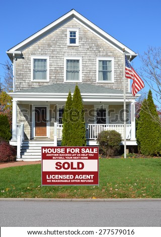 Real estate sold (another success let us help you buy sell your next home) sign Beautiful Gable style  Suburban Home Sunny Autumn clear blue sky day residential neighborhood USA - stock photo