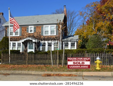 Real estate sold (another success let us help you buy sell your next home) sign Beautiful Suburban Georgian style home wood shingles fence sunny clear blue sky autumn day residential neighborhood USA - stock photo