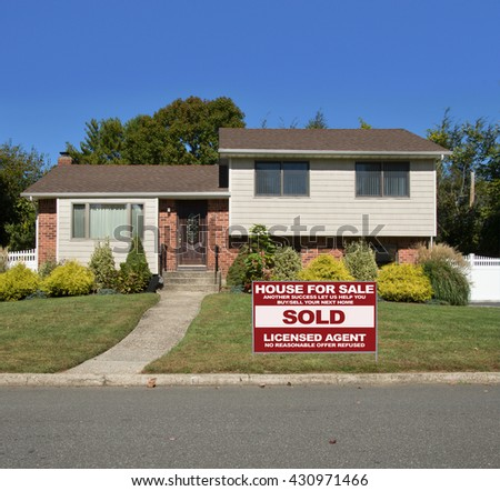 Real estate sold (another success let us help you buy sell your next home) sign Beautiful Suburban High Ranch Aluminum Siding Brownstone Brick Home residential neighborhood clear blue sky USA