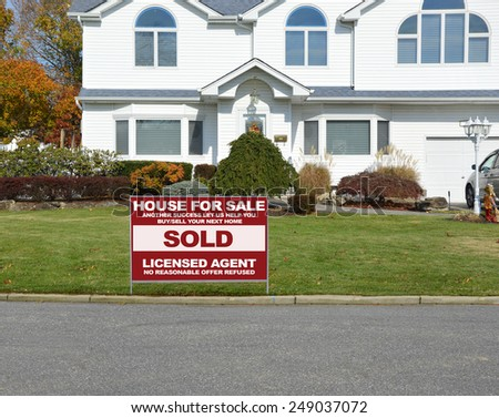 Real estate sold (another success let us help you buy sell your next home) sign closeup of suburban mcmansion autumn day residential neighborhood USA