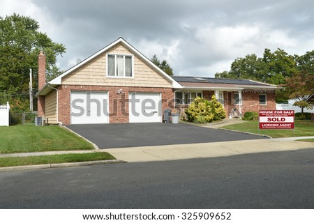 Real estate sold (another success let us help you buy sell your next home) sign  suburban brick brownstone ranch home two car garage overcast cloudy sky residential neighborhood USA - stock photo