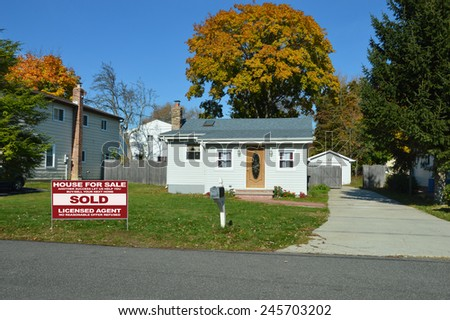 Real Estate sold (another success let us help you buy sell your next home) sign Suburban bungalow home sunny autumn clear blue sky day residential neighborhood USA - stock photo