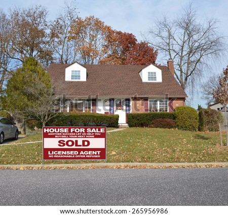 Real estate sold (another success let us help you buy sell your next home) sign Suburban cape cod style home residential neighborhood USA - stock photo